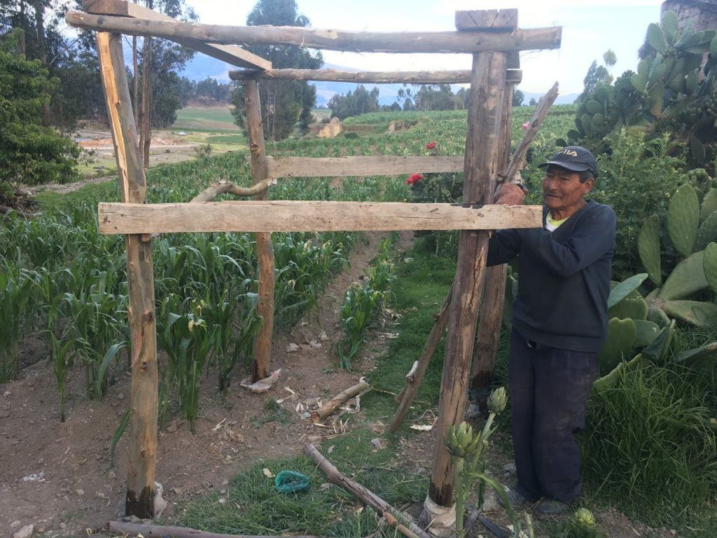 Water tank beneficiary, Jose, shows off the platform he helped construct for his family. Made out of eucalyptus tree trunks and some scrap wood.