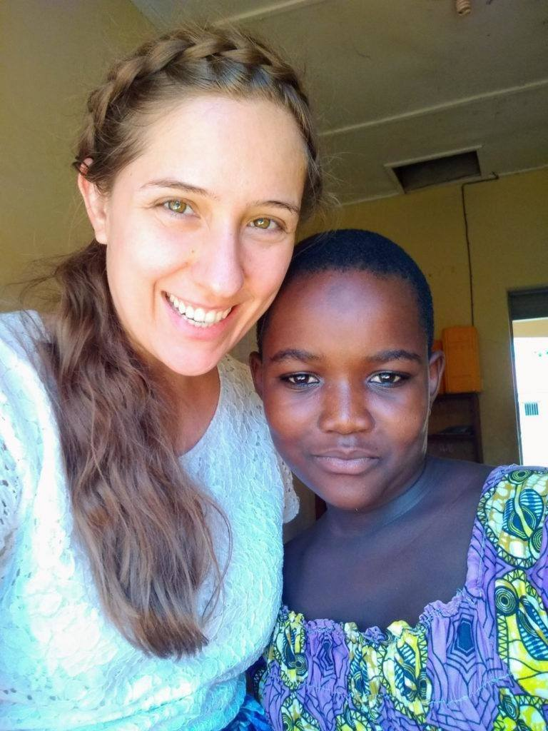 Angela at school, posing for a photo with one of her students