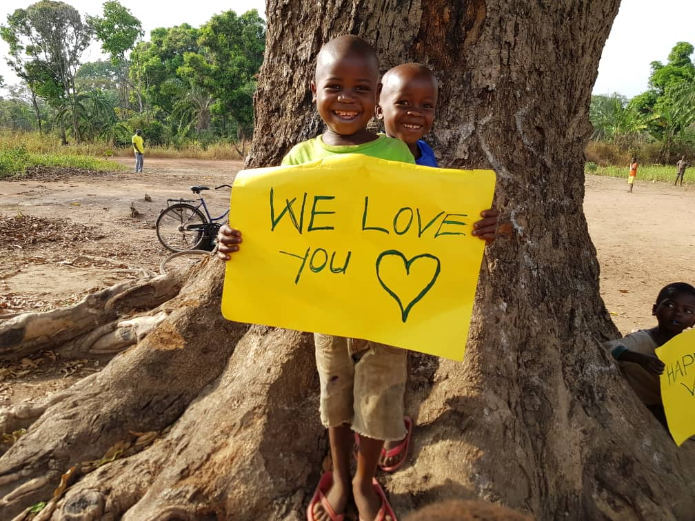 Boy from South Sudan with friend holding Valentines Day sign