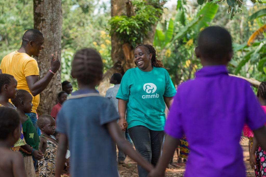 Catherine in a CMMB shirt, leading a CFS activity with community children