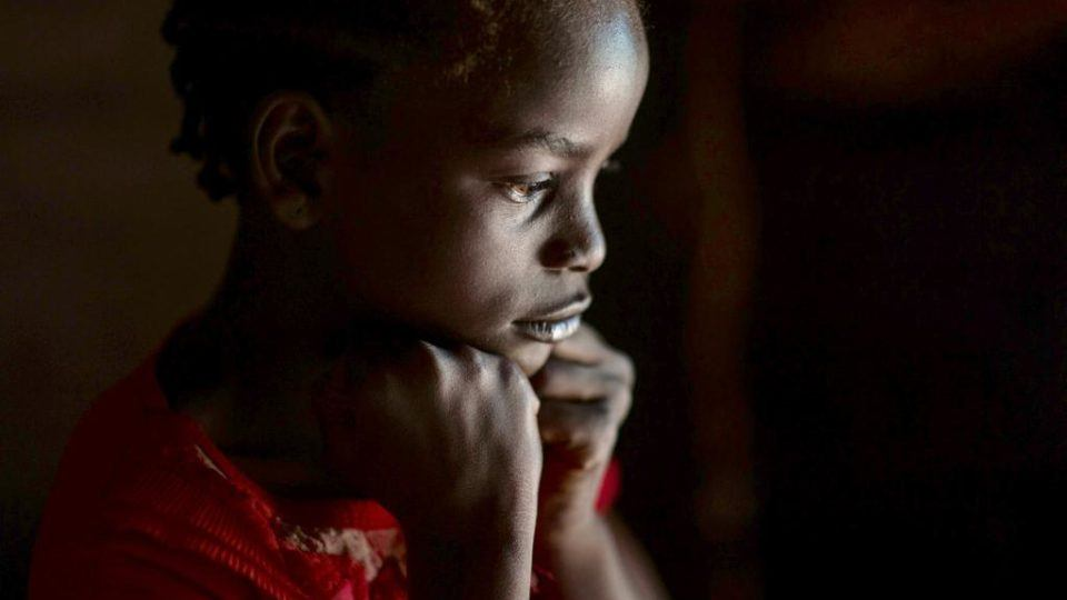 A young child sits looking sad and pensive. There is a light that casts on her face. She is a former child soldier in South Sudan