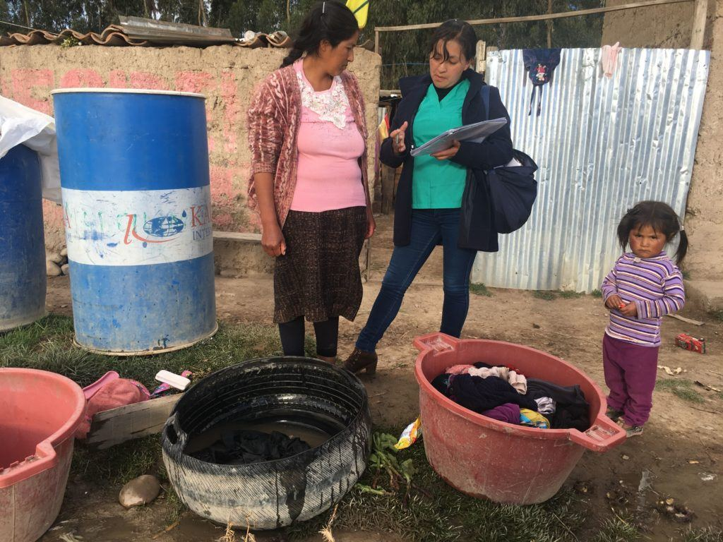 Gina speaking with a community mother, teaching her practices for WASH intervention