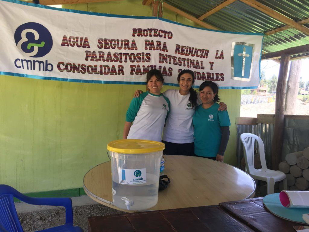 Jolynn and two CMMB Peru staff members prepare for a WASH presentation. They stand in front of a CMMB banner