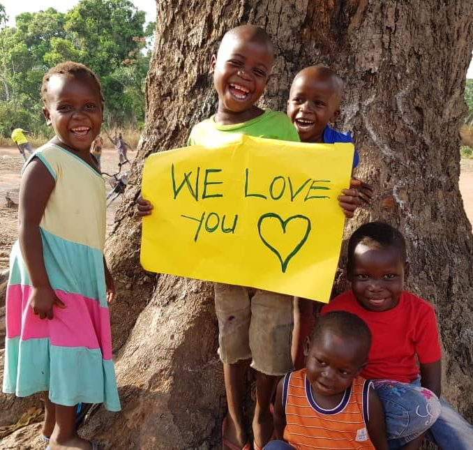 South Sudanese boy with multiple friend holding Valentines Day sign