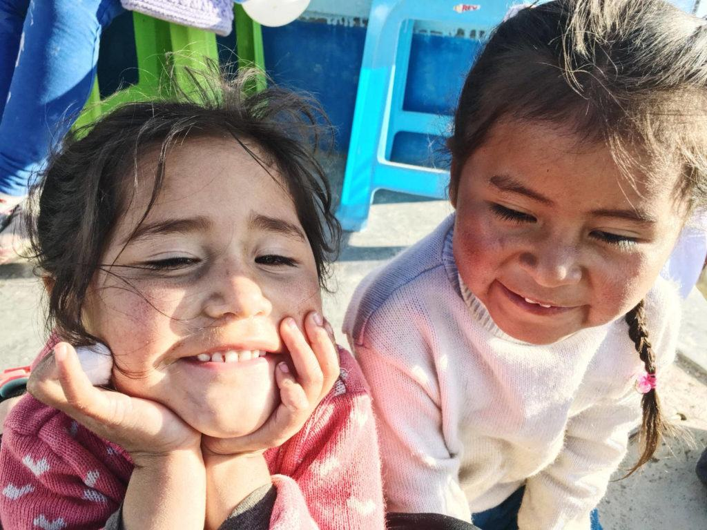Two little girls in Peru, sitting beside one another and smiling