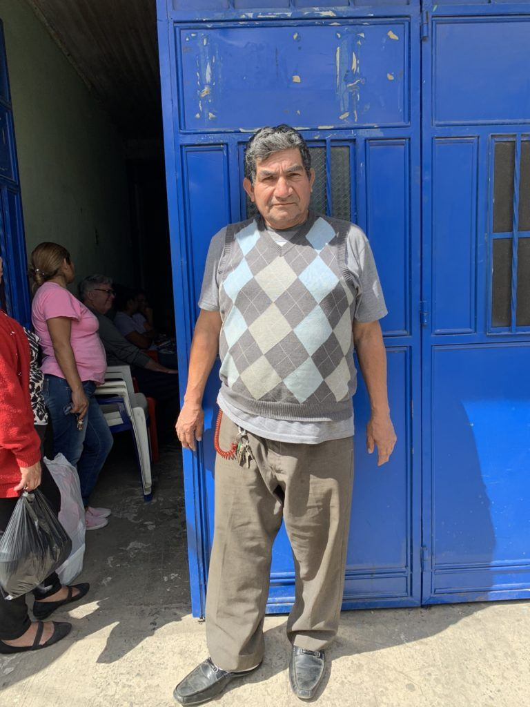Image of a patient at the Santa Isabella Clinic. He stands in front of a blue door