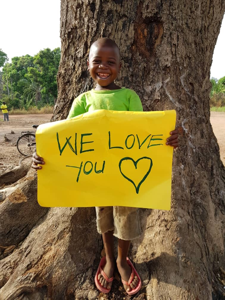We love you sign held by South Sudanese boy