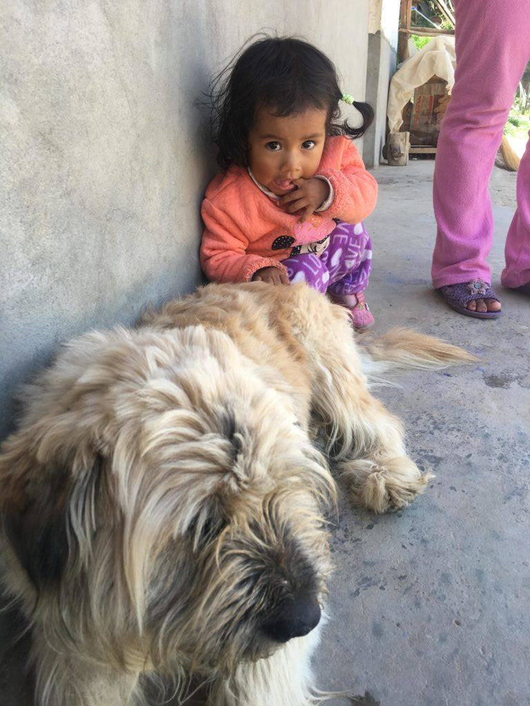Mia, a young girl served in Peru, sitting with a puppy