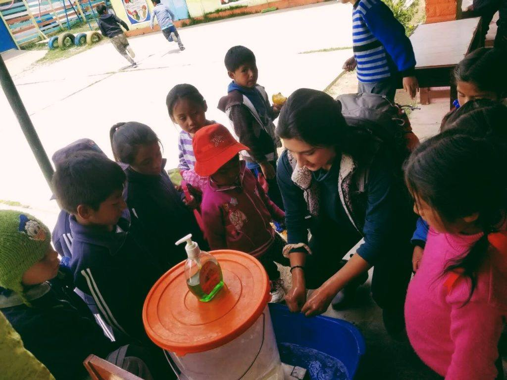 Vollunteer Jolynn demonstrating how to properly wash hands to young children in Peru