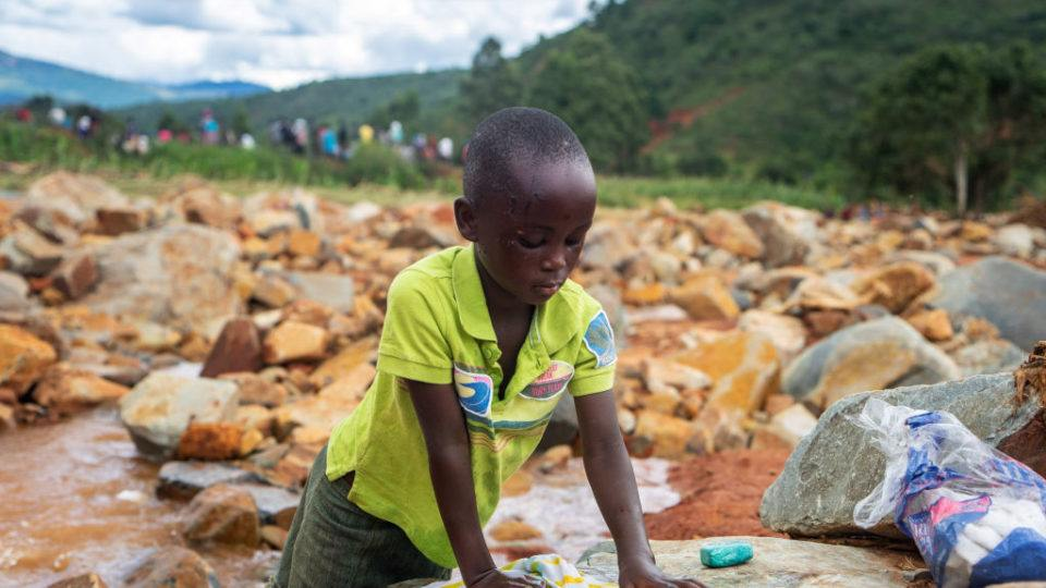 A young girl washes in a stream her donated dress near the Chimanimani Rural Hospital where displaced people following cyclone Idai are sheltered on March 20, 2019. CMMB response to the situation.
