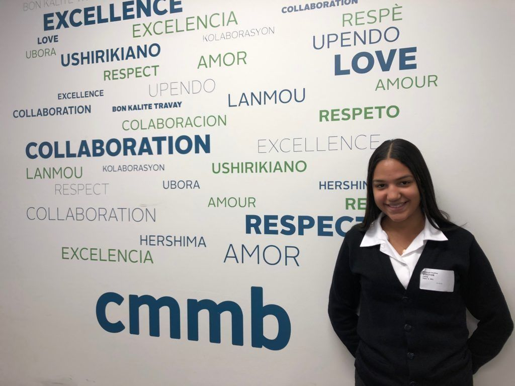 Crissy is a Cristo Rey intern posing in frnr of a wall featuring CMMB's values.