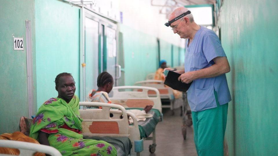 Dr. James Peck talks to a female patient in the maternity ward at Mother of Mercy Hospital in Sudan.