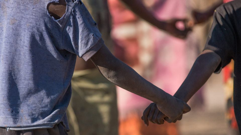 Children holding hands. They are playing in their villiage in Mwandi, Zambia