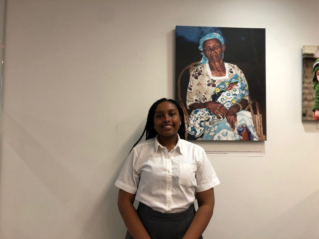 Munimatu posing in front of white wall with canvas photo in the background. She is one of our 2018-2019 Cristo Rey Interns