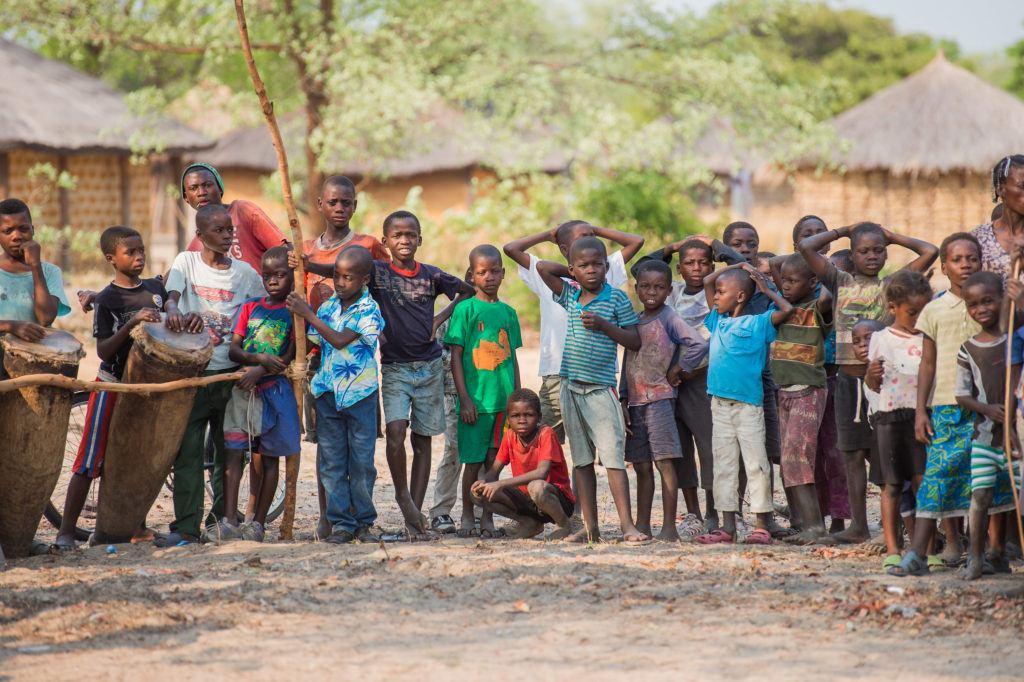 A group of children in Zambia standing together. In the background are homes and trees