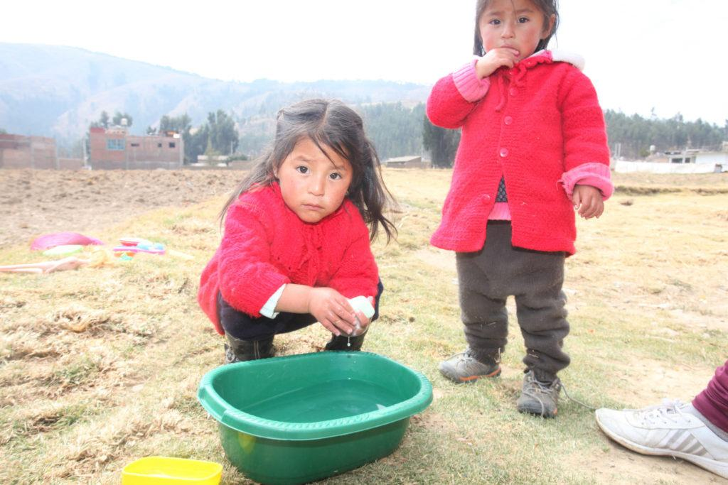Two girls in Peru washing their hands