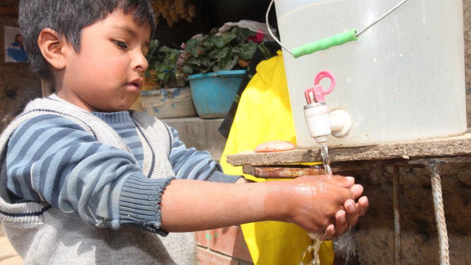 Little boy in Peru washing his hands