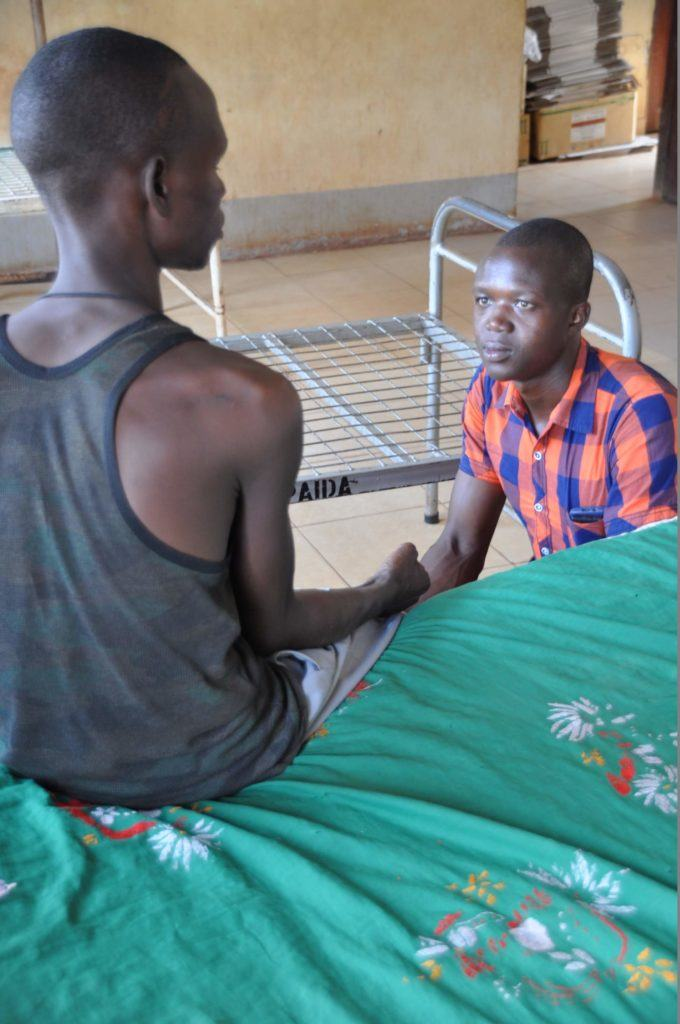 A health worker taught by Dr. Dan helps a patient