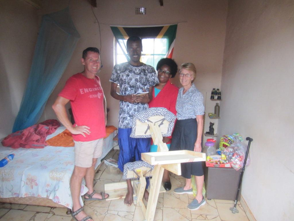Khulani trying out his seat with Kathleen and the Operation Hope team