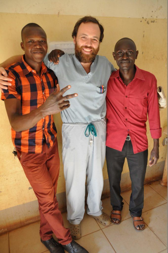 Dr. Dan and two of his students stand against the hospital wall for a photo