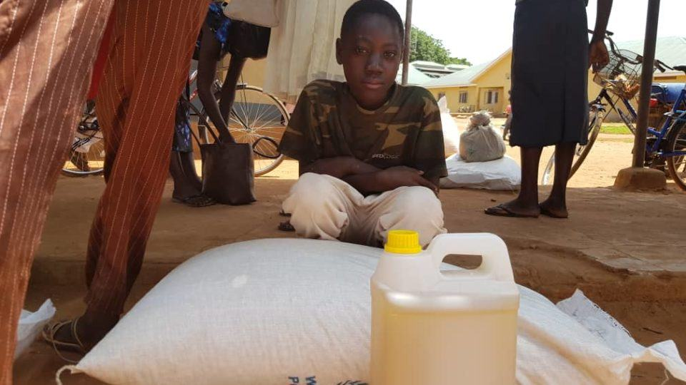 Moses, a young boy served by CMMB, sitting in front of food donation