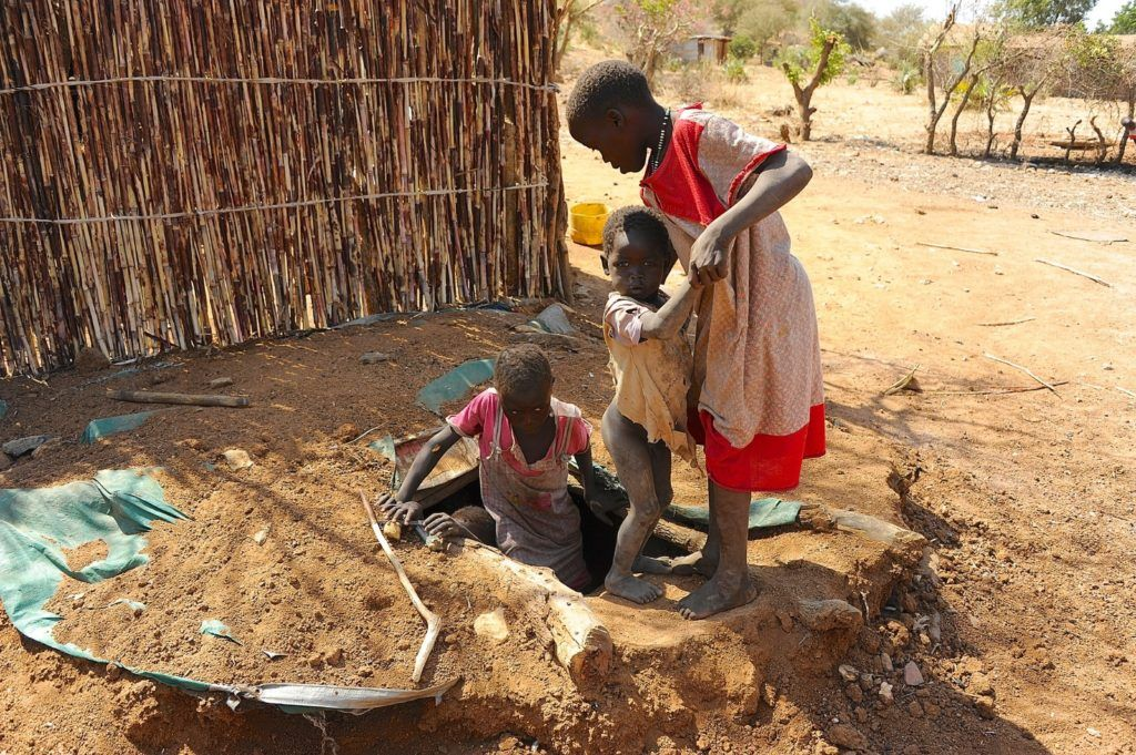 Children in the Nuba Mountains climbing into fox holes for shelter