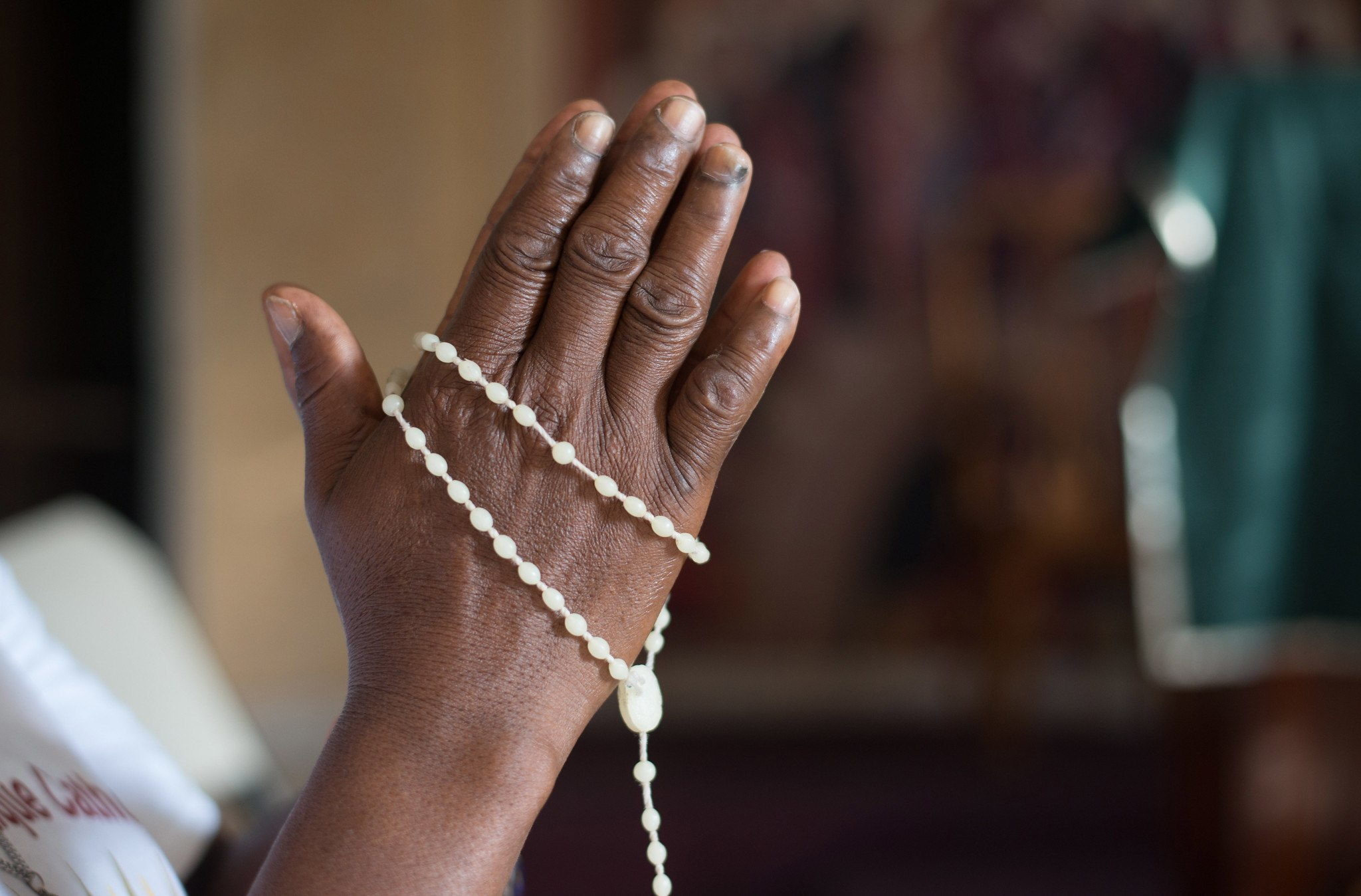Hands praying with rosary around the rosary