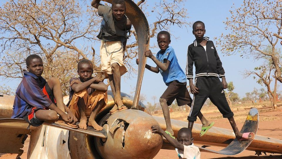 Nuba children standing and sitting on a crashed and abandoned plane