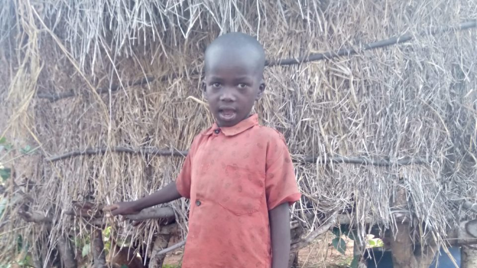 eric six year old from kenya in front of his house
