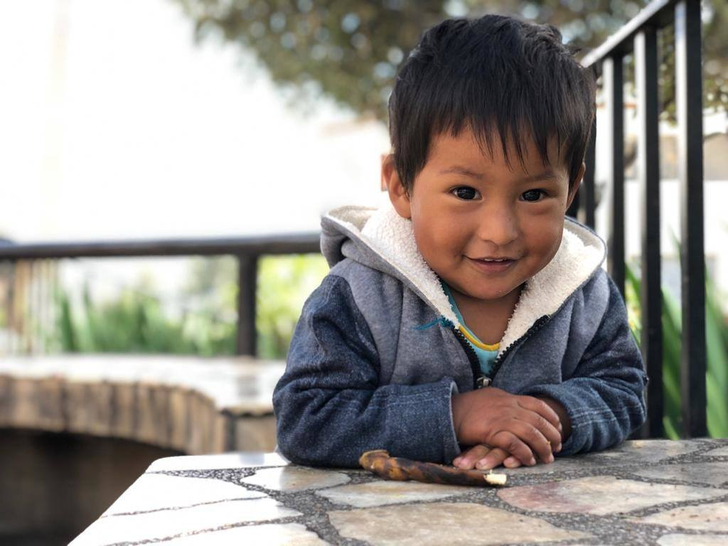 A little boy sits at a table in Peru
