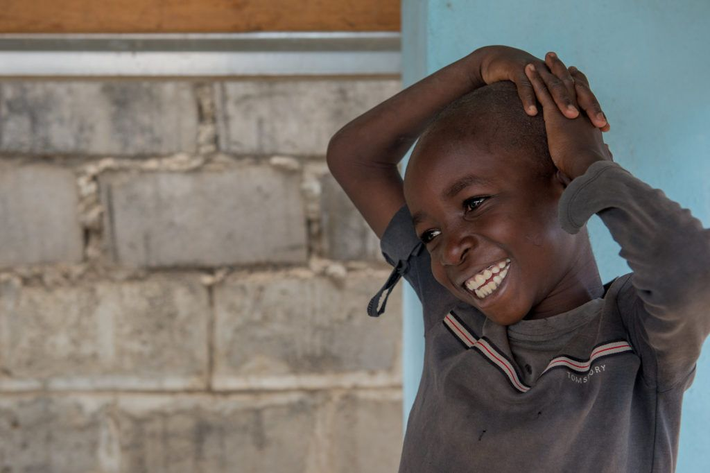 A little boy smiles with his hands on his head