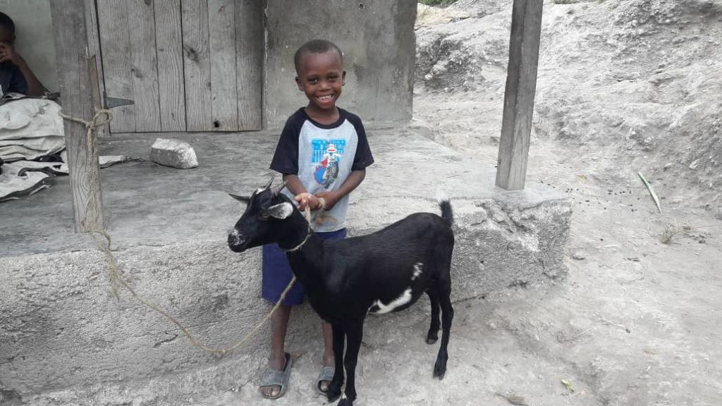 a little boy in Kenya holding the leash for his family goat