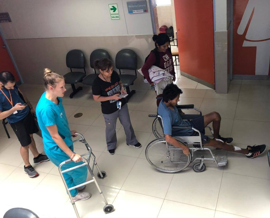 A look at a patient who is being treated by CMMB And the ISHI team. The patient is in a wheelchair and four staff members help him