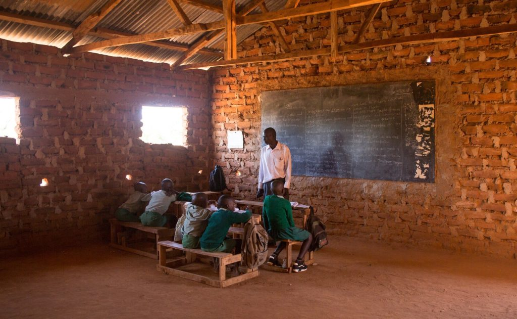 A teacher teaching his students. They are in a classroom made of brick