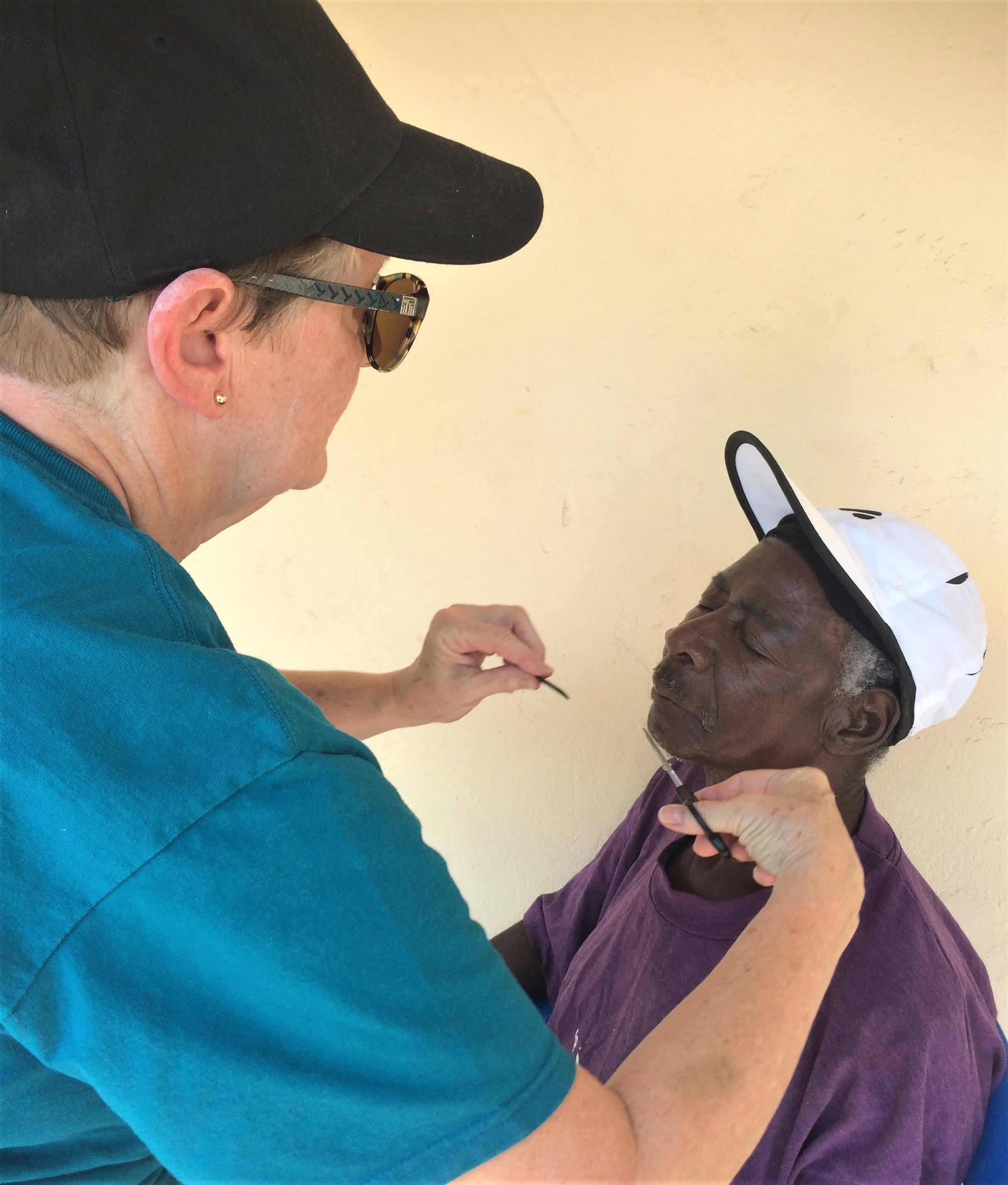 cmmb volunteer Beverly trims a patient's beard