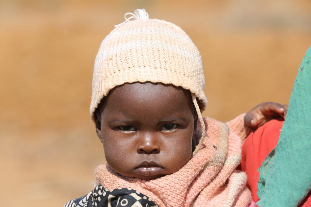 A young child with a pink hat is held in her mother's arms in Kenya. She is looking a little grumpy.