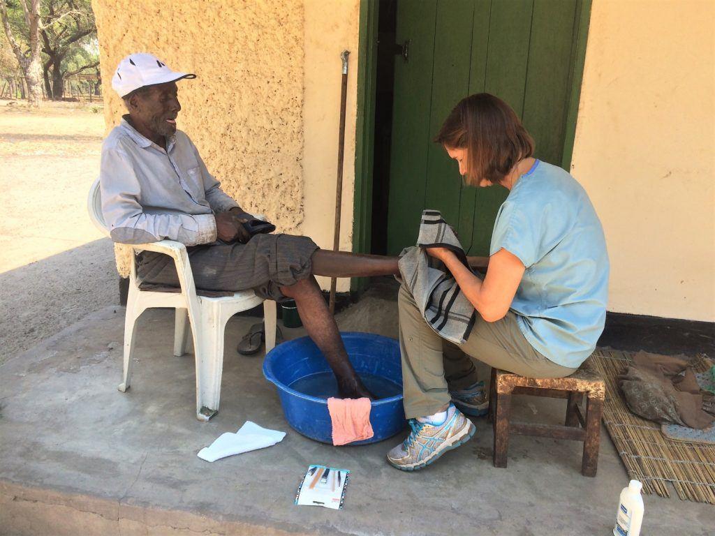 Dr Helene cleans a patients feet in Mwandi, Zambia