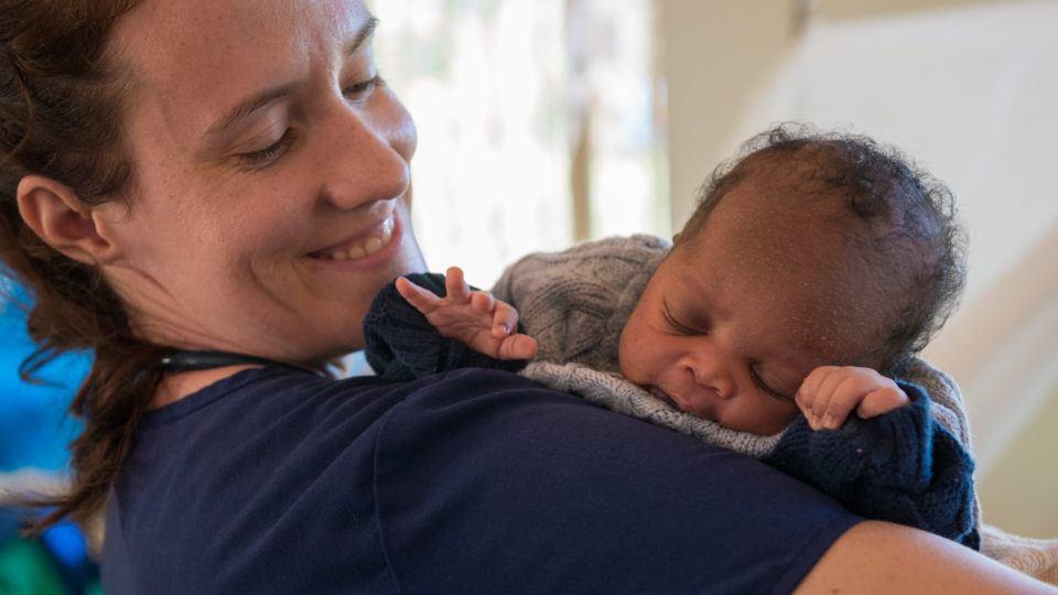 Sarah Rubino holds a newborn baby in Nzara South Sudan