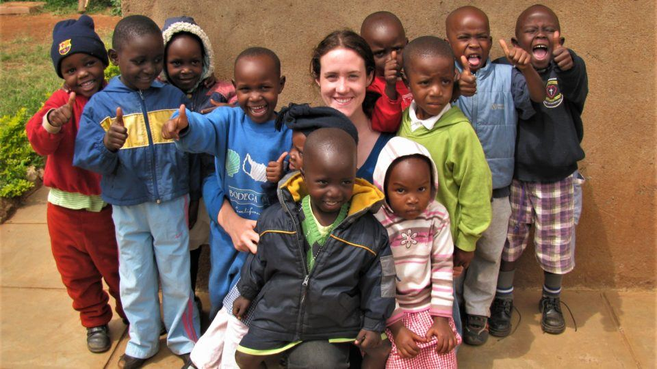Sarah surrounded by children she served on her first volunteer trip