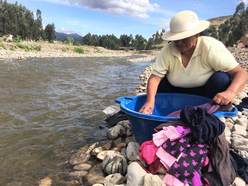 woman washing clothes by the river in tambo huari peru