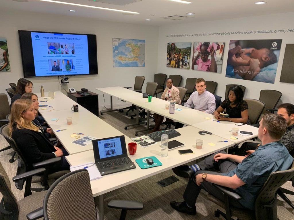 2019 Summer interns learning all about CMMB. They sit together at a conference table for a presentation