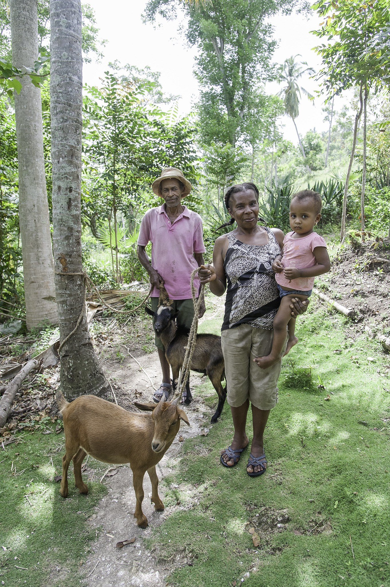A family in Haiti poses with their goats