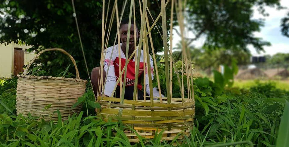 A young boy sits behind a almost completed basket