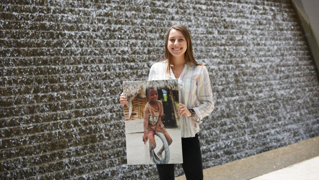 Carley - a cmmb intern poses outside with an image of a child we serve