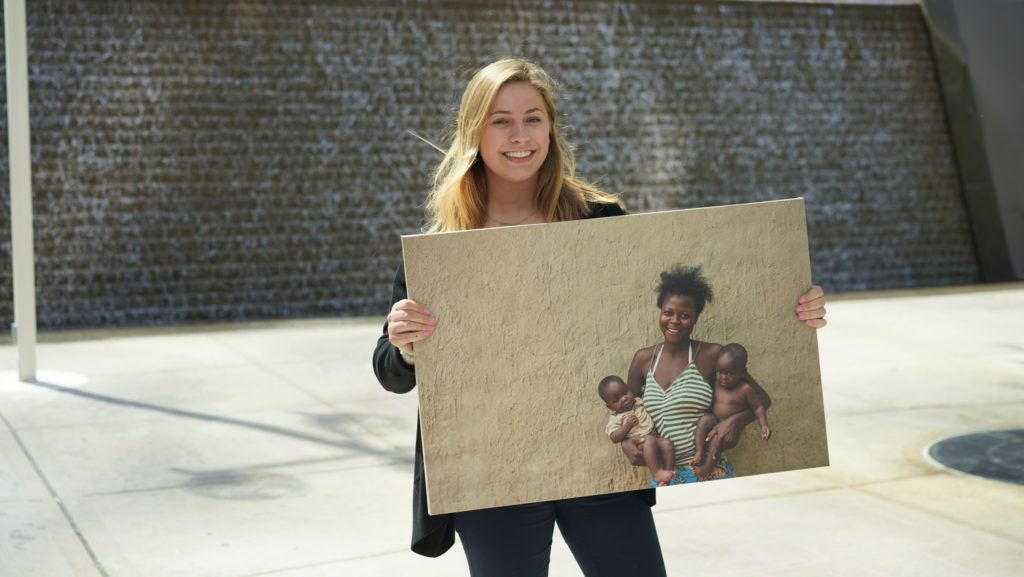Chloe, a CMMB intern poses outside with a photo of individuals we serve