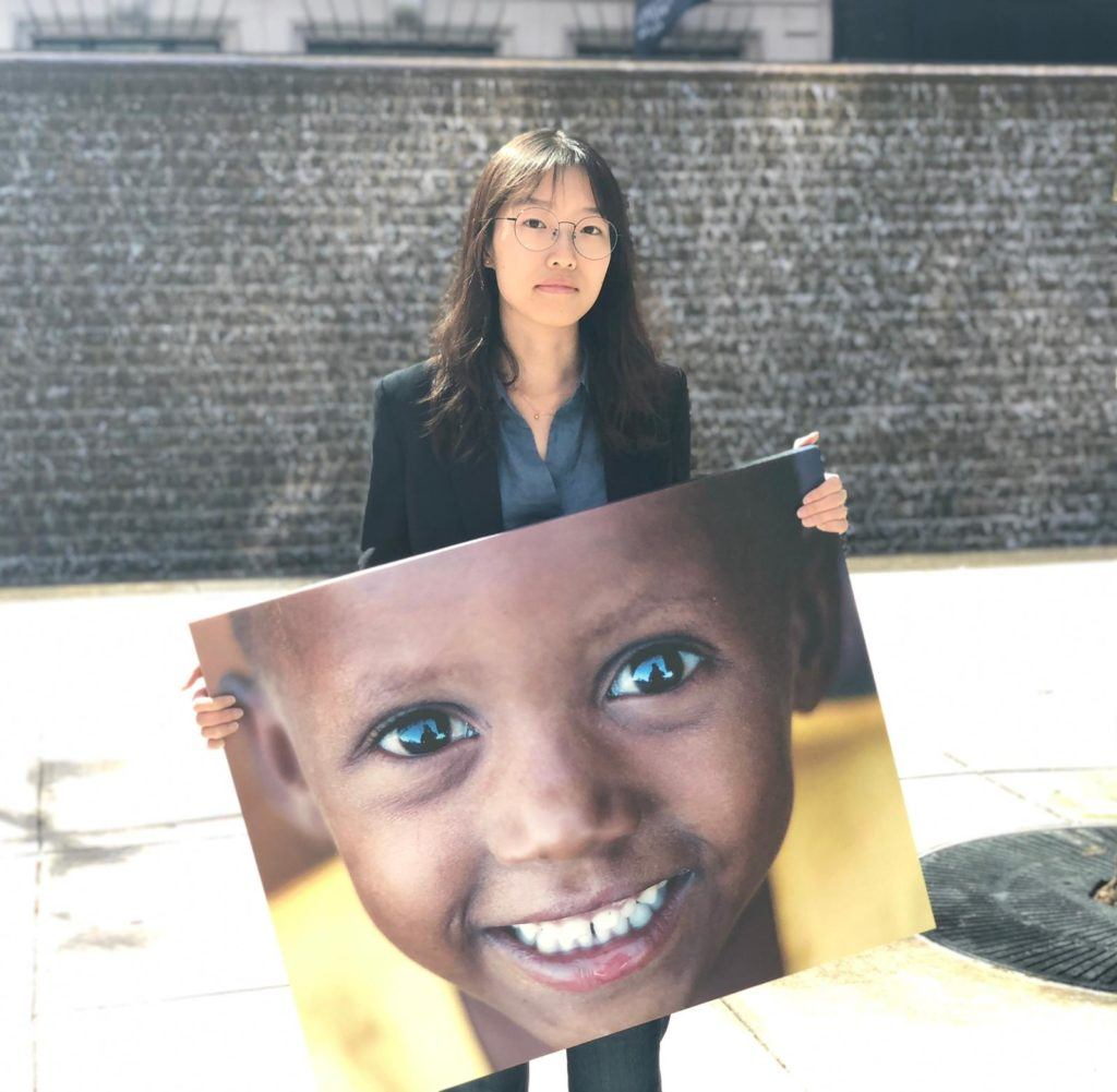 Chu, a summer intern, poses outside with a canvas image of one of the children we serve