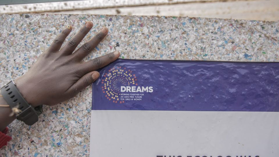 A hand holding up a DREAMS sign agains a gray background