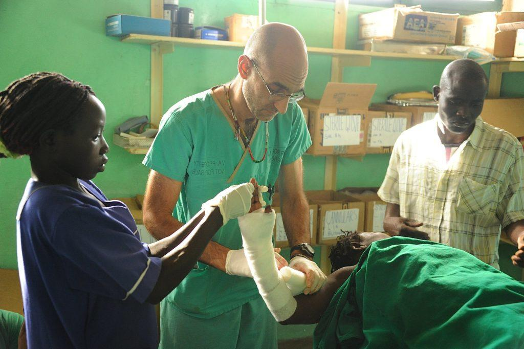Dr. Tom is dressing a Nuba Person's arm injury
