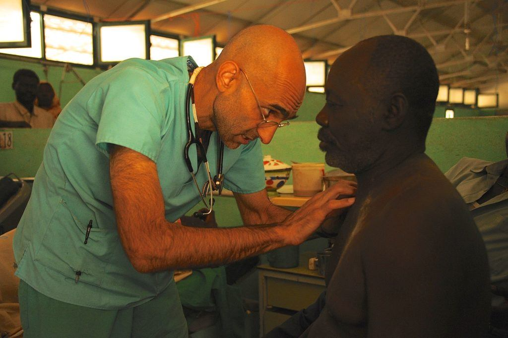Dr. Tom leans over a patient to treat him.