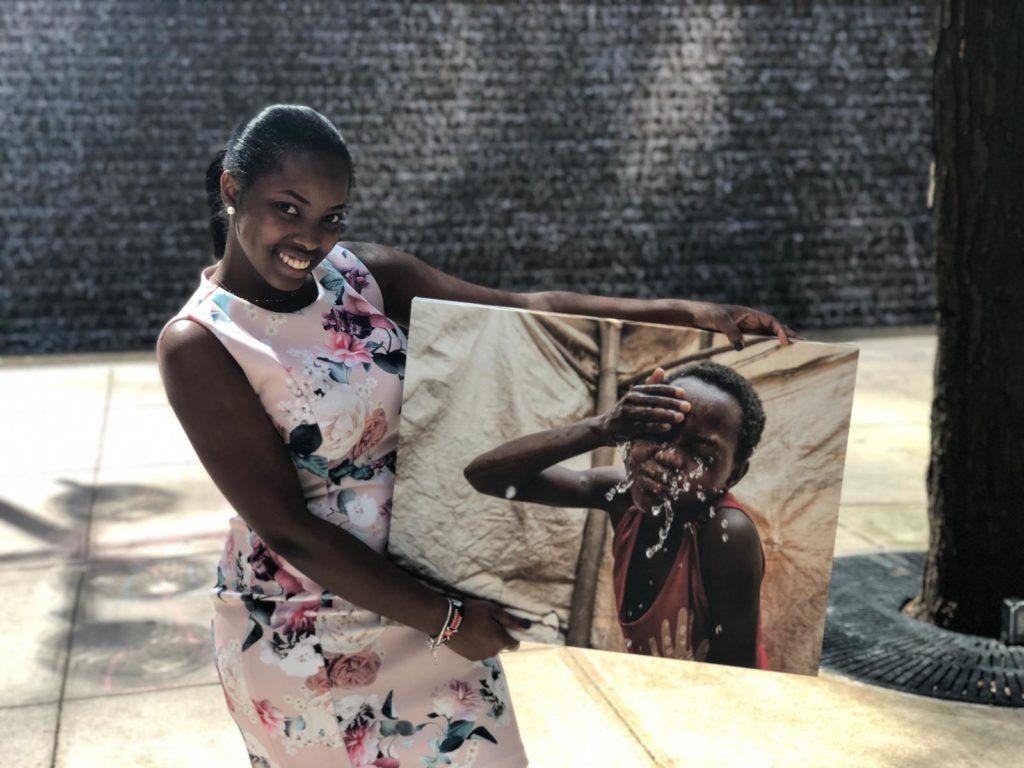 Edna Nthenya, a CMMB intern posing outside with an image of an individual we serve